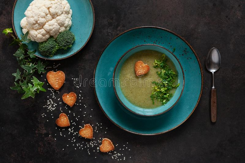 Vegetarian cauliflower and broccoli homemade cream-soup with seeds, heart shape crackers and fresh seasoning and vegetables. royalty free stock image