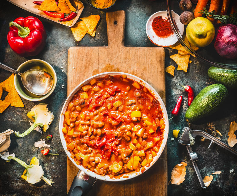 Vegetarian chili con carne dish in pan on wooden cutting board with spices and vegetables cooking ingredients on dark kitchen tabl. E background, top view royalty free stock photo