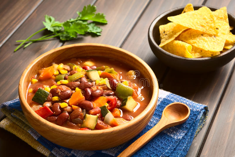 Vegetarian Chili Dish. Wooden bowl of vegetarian chili dish made with kidney bean, carrot, zucchini, bell pepper, sweet corn, tomato, onion, garlic, with royalty free stock images