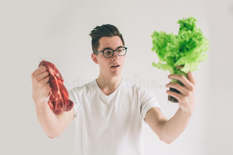 Vegetarian concept. Man offering a choice of meat or vegetables Salad leaves . Nerd is wearing glasses. royalty free stock images