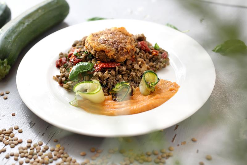 Vegetarian cooking. Colorful vegetable meatless dish. Boiled lentils with carrot puree and grilled zucchini stock photo