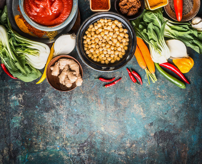 Vegetarian cooking ingredients with chick peas dish, spicy indian curry paste , greens, ginger and vegetables on rustic background. Top view, border. Healthy stock images