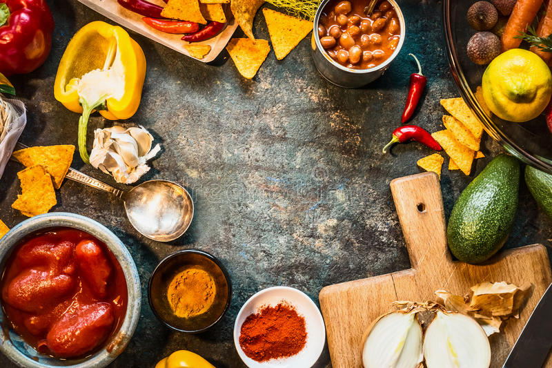 Vegetarian cooking ingredients for Mexican cuisine: canned Beans, Peeled tomatoes, paprika,chili, onion,lemon, spices , avocado an. D tacos or tortilla chips on stock photos