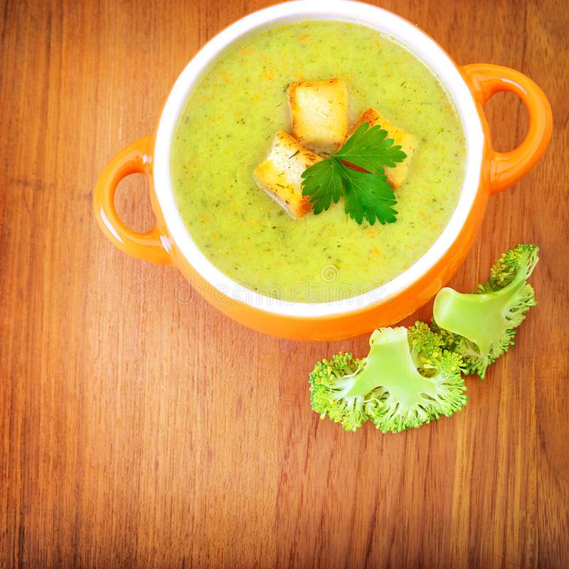 Vegetarian cream soup. Ceramic pot with tasty vegetarian creamy soup on wooden table, two pieces of fresh green broccoli, healthy eating, diet concept stock photo