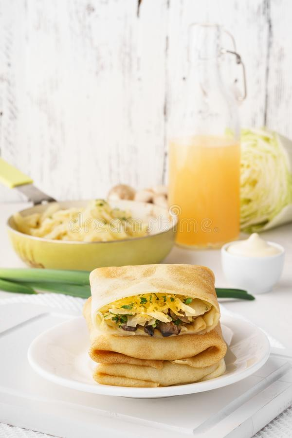 Vegetarian crepes with cabbage, mushrooms and cheese filling royalty free stock photo