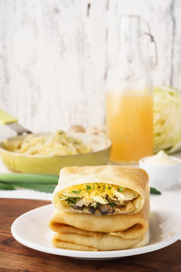 Vegetarian crepes with cabbage, mushrooms and cheese filling royalty free stock photography