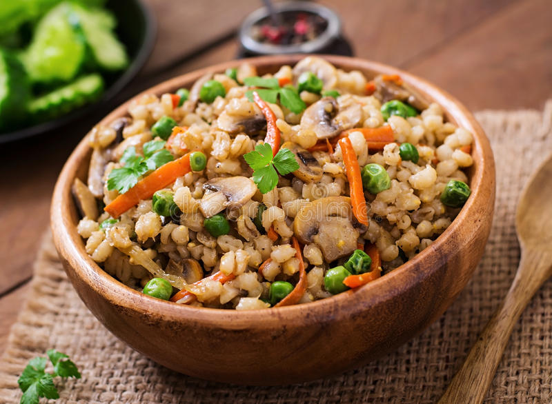 Vegetarian crumbly pearl barley porridge. With mushrooms and green peas in a wooden bowl stock photography
