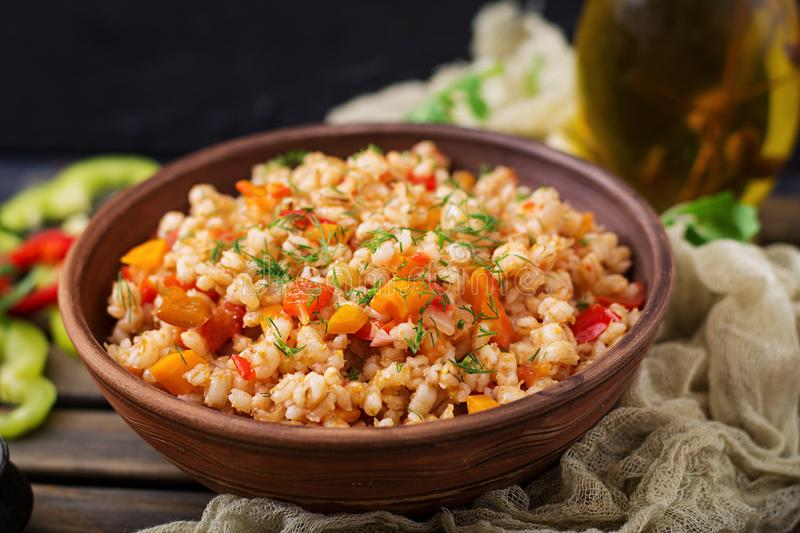 Vegetarian crumbly pearl barley porridge with vegetables. In a dark background royalty free stock image