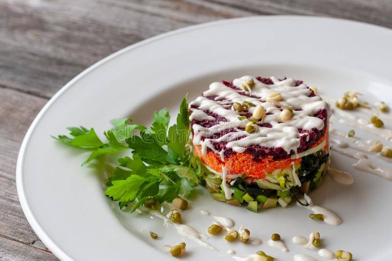 Vegetarian dish: layered salad of wakame, beets, carrots, zucchini, avocados, greens, mayonnaise and sprouted seeds. Creative dish royalty free stock image