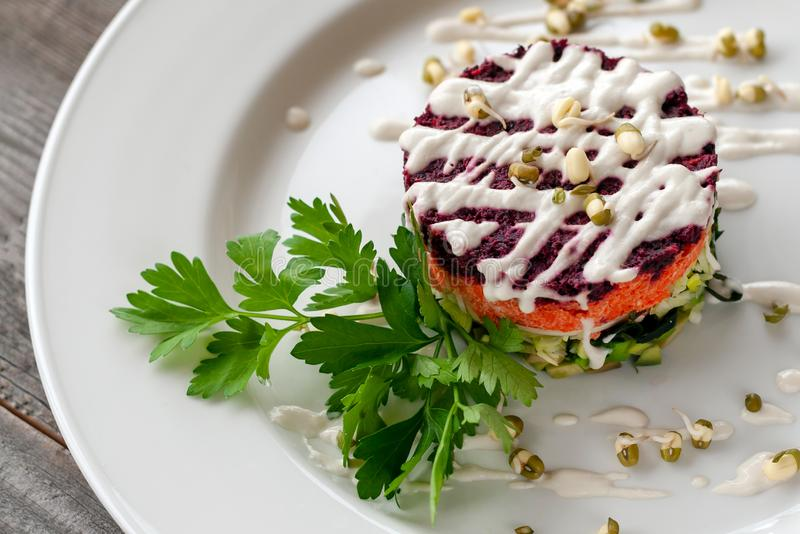 Vegetarian dish: layered salad of wakame, beets, carrots, zucchini, avocados, greens, mayonnaise and sprouted seeds. Creative dish royalty free stock photography