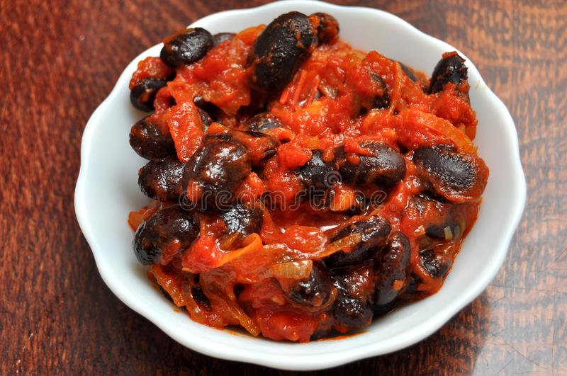 Vegetarian dish of stewed carrot and black beans with a tomato sauce in a white ceramic bowl on a wooden table stock images