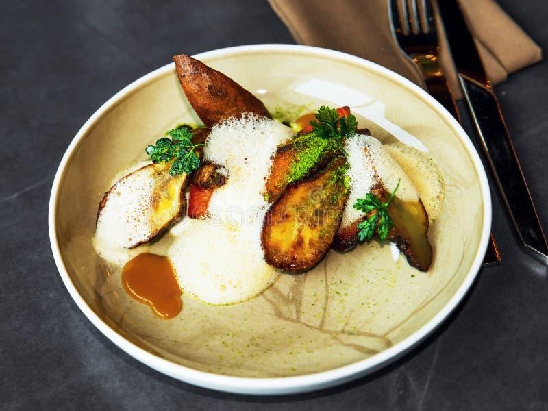Vegetarian dish with topinambour, sweet potato, parsley, miso and foam, high gastronomy. Vegetarian plate with jeruzalem artychoke (topinambour), sweet potato ( royalty free stock photo