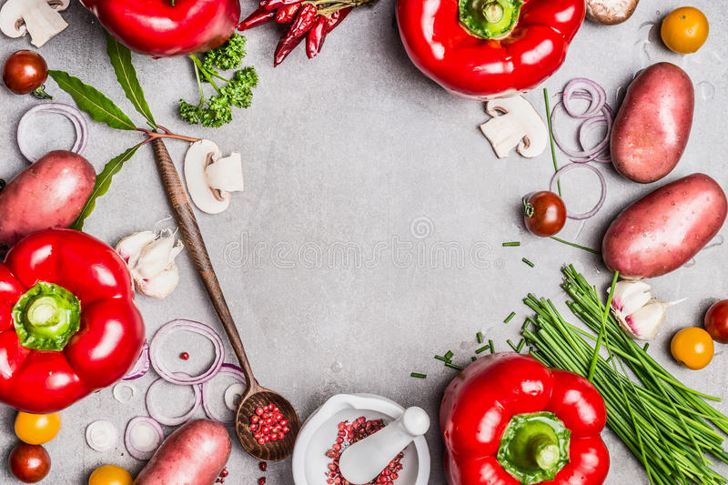 Vegetarian food background with various organic vegetables, wooden spoon and seasoning for tasty cooking. Top view composing, fra royalty free stock photo