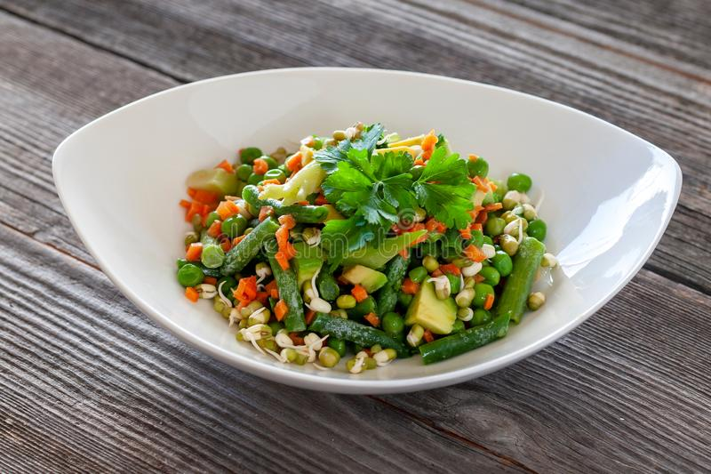 Vegetarian food: Beautiful delicious salad with avocado, broccoli, carrot, green peas, green beans with sprouted seeds. Raw foods royalty free stock image