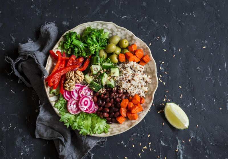 Vegetarian food bowl. Quinoa, beans, sweet potatoes, broccoli, peppers, olives, cucumber, nuts - healthy lunch. On the dark table royalty free stock images