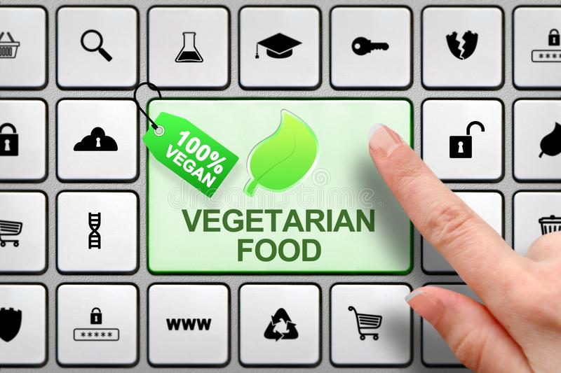 Vegetarian food concept, girl`s finger above the big button on the keyboard stock photos