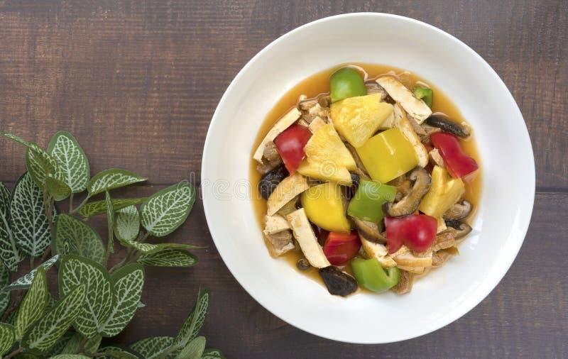 Vegetarian food,fried sweet bell pepper with pine-apple,mushroom,tofu put in white ceramic plate. stock image