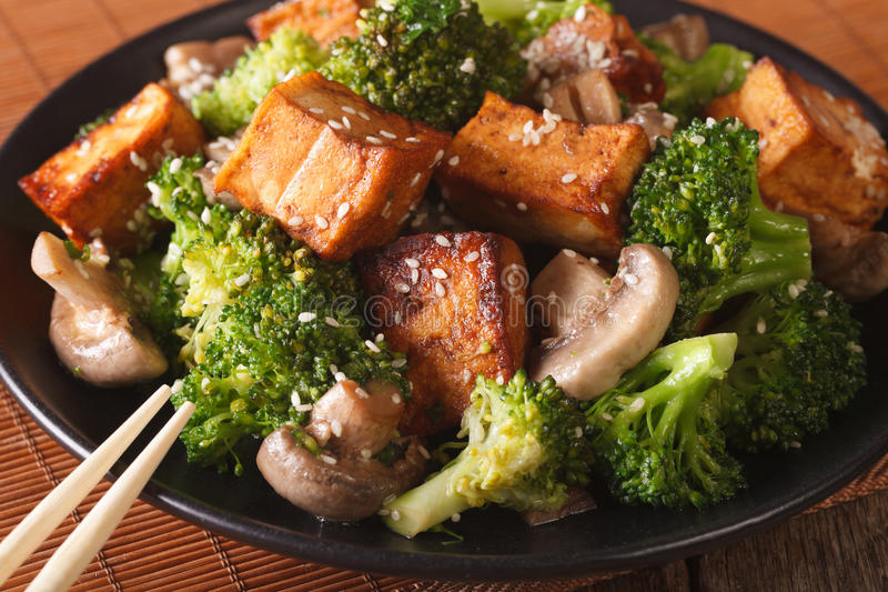 Vegetarian food: fried tofu with broccoli, mushrooms and sesame royalty free stock photos