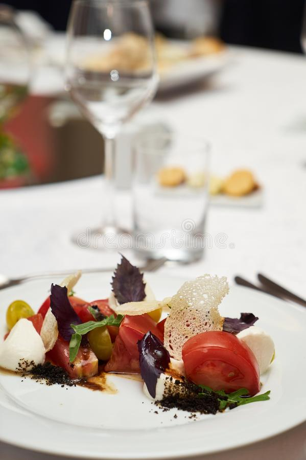Vegetarian food with marinated tomatoes, arugula, mozzarella che. Ese, balsamic jelly, olive oil. Delicious healthy food concept, close-up royalty free stock images