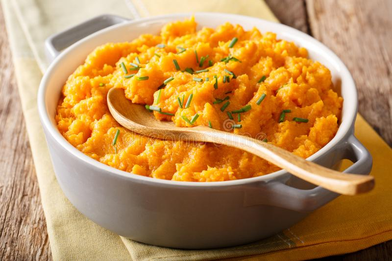 Vegetarian food: mashed sweet potatoes with herbs close-up on a. Vegetarian food: mashed sweet potatoes with herbs close-up in a saucepan on a table. horizontal royalty free stock images