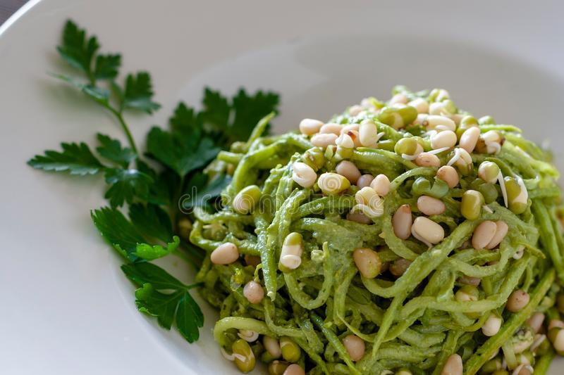 Vegetarian food: vegetable spaghetti from zucchini, sprouted see. Ds with green sauce and pesto sauce. Healthy food royalty free stock images