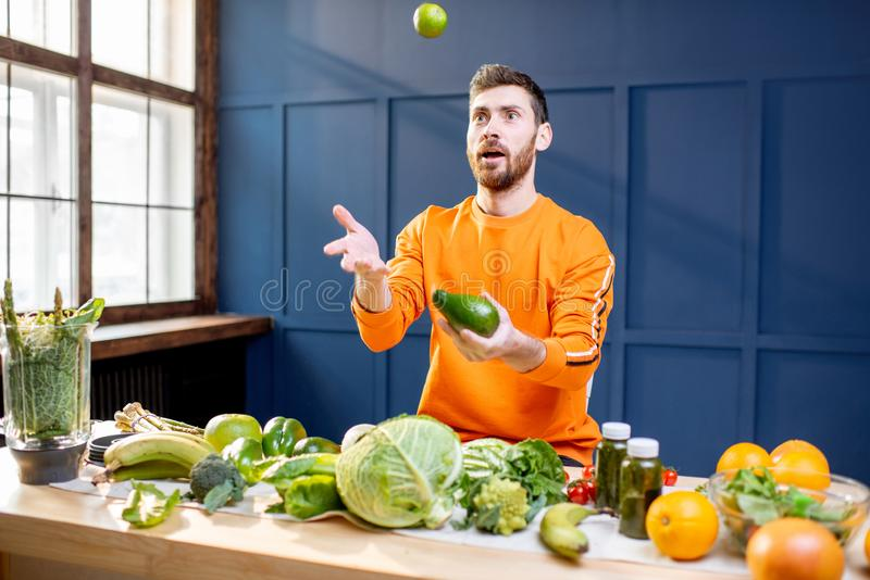 Vegetarian with fresh vegetables on the blue background. Conceptual portrait of a vegetarian man in bright sweater throwing up vegetables on the blue background royalty free stock photography