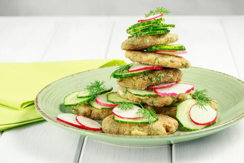 Vegetarian fried zucchini pancakes, asparagus and greens served with cucumbers and radishes stock photo