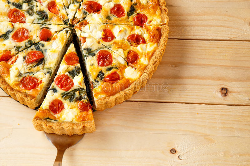Vegetarian homemade pie, Quiche with tomatoes, spinach and feta cheese. Vegetarian homemade pie, Quiche with tomatoes, spinach and feta cheese royalty free stock photos