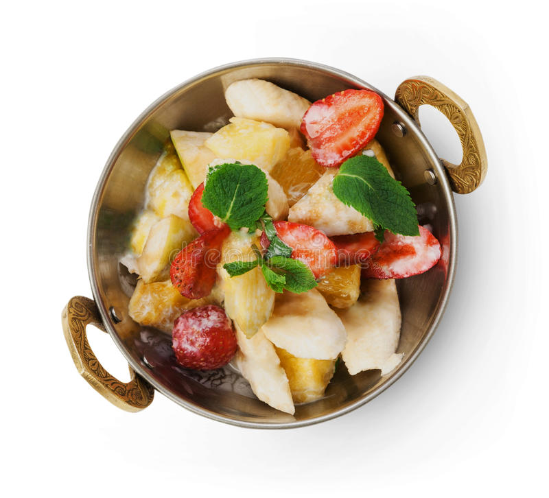 Vegetarian indian restaurant dish, fresh fruit and strawberry salad isolated. Vegan and vegetarian dish, fresh fruit and strawberry salad in copper bowl closeup royalty free stock images