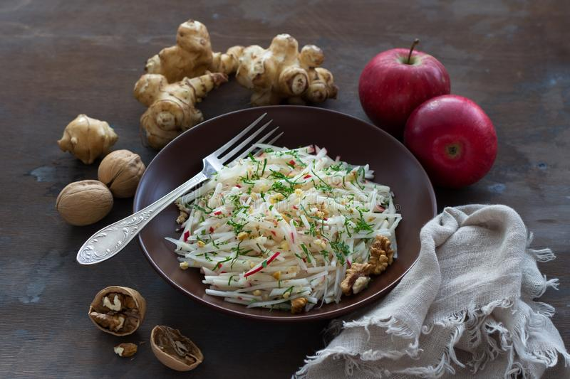 Vegetarian Jerusalem artichoke topinambour salad with apple, walnut and greens. On a dark wooden background, free space. healthy diet food stock photos