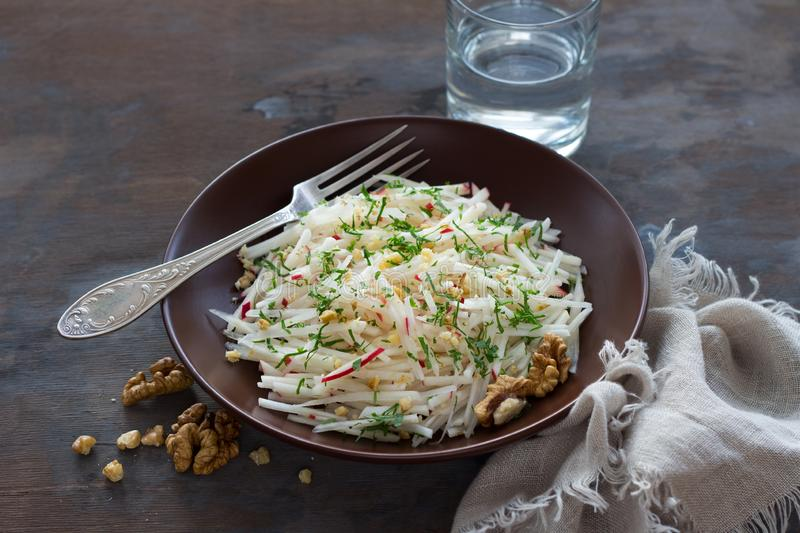 Vegetarian Jerusalem artichoke topinambour salad with apple, walnut and greens. On a dark wooden background, free space. healthy diet food royalty free stock photo
