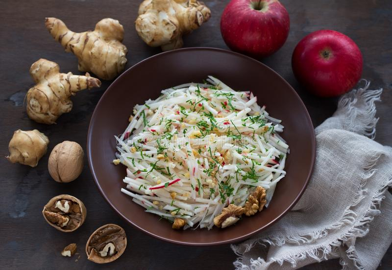Vegetarian Jerusalem artichoke topinambour salad with apple, walnut and greens. On a dark wooden background, free space. healthy diet food stock image