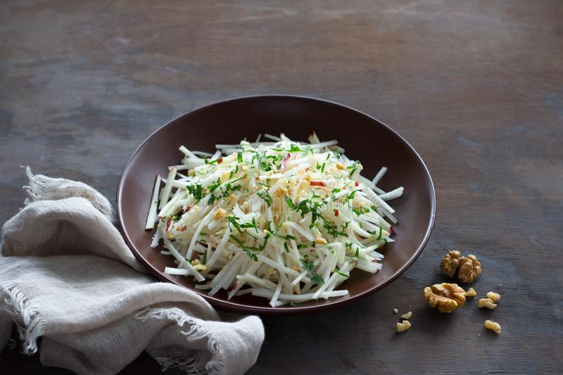 Vegetarian Jerusalem artichoke topinambour salad with apple, walnut and greens on a dark wooden background. Free space. healthy diet food stock photos