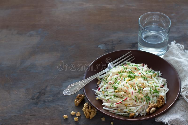 Vegetarian Jerusalem artichoke topinambour salad with apple, walnut and greens. On a dark wooden background, free space. healthy diet food stock images