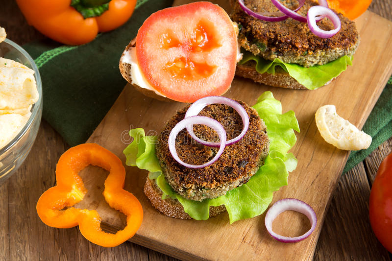 Vegetarian lentil burger. With vegetables on wooden cutting board - healthy vegan organic vegetarian diet fast food burger lunch stock photography
