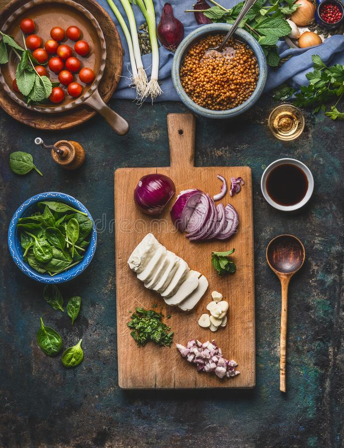 Vegetarian lentil dishes cooking preparation on rustic kitchen table background with cutting board, cooking spoon and utensils, to. P view. Healthy eating and stock image