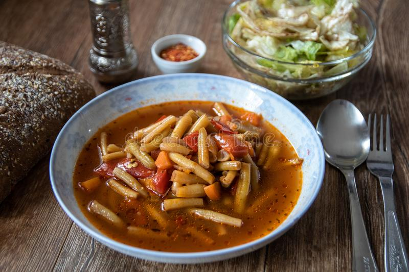 Vegetarian lunch. Green bean soup with tomato sauce and vegetables royalty free stock photo