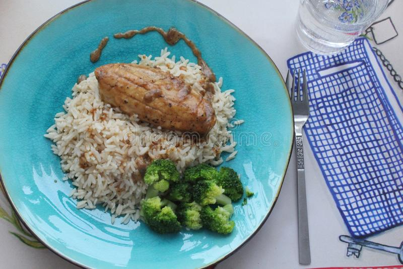 Vegetarian lunch. With rice, filé and broccoli on a turquoise plate royalty free stock photos