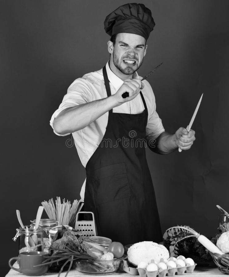 Vegetarian meal concept. Chef with angry face holds metal knives. Vegetarian meal concept. Chef with angry face holds blue and metal knives on dark green stock images