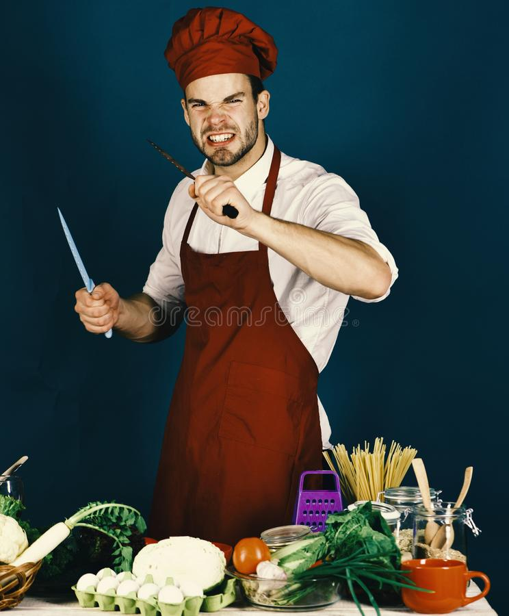 Vegetarian meal concept. Chef with angry face holds metal knives. Vegetarian meal concept. Chef with angry face holds blue and metal knives on dark green stock photography
