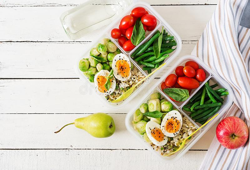 Vegetarian meal prep containers with eggs, brussel sprouts, green beans and tomato. Dinner in lunch box. Top view. Flat lay royalty free stock photos