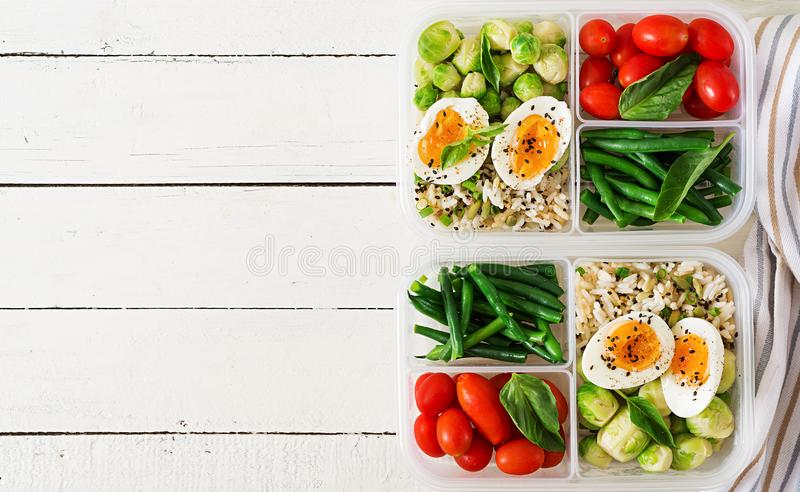 Vegetarian meal prep containers with eggs, brussel sprouts, green beans. And tomato. Dinner in lunch box. Top view. Flat lay stock images