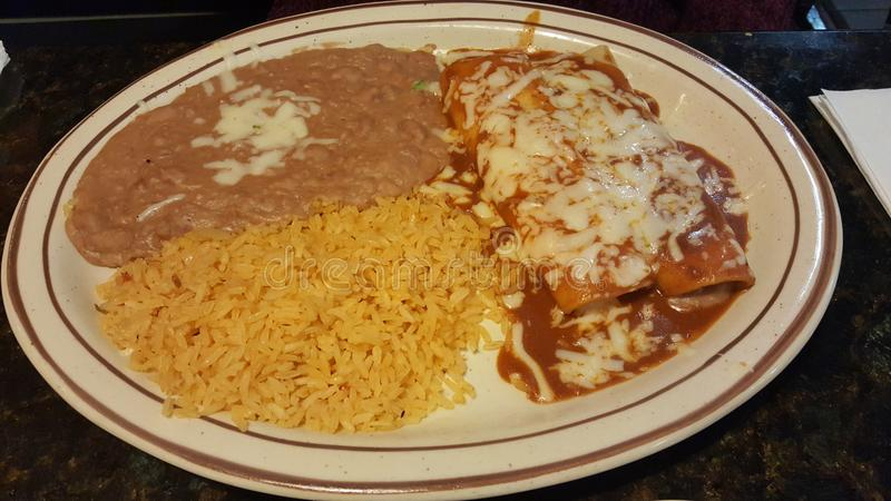 Vegetarian Mexican food with rice and enchilada. Vegetarian Mexican food with rice and beans, and cheese enchilada with sauce stock photography