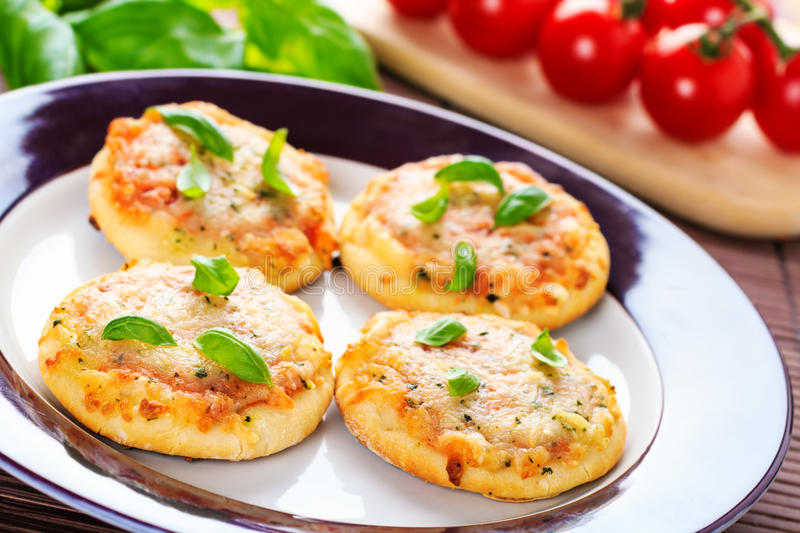 Vegetarian mini pizzas. Homemade vegetarian mini pizzas served on a wooden board stock photos