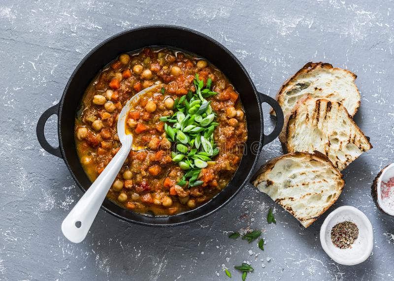 Vegetarian mushrooms chickpea stew in a iron pan and rustic grilled bread on a gray background, top view. Healthy vegetarian food stock images