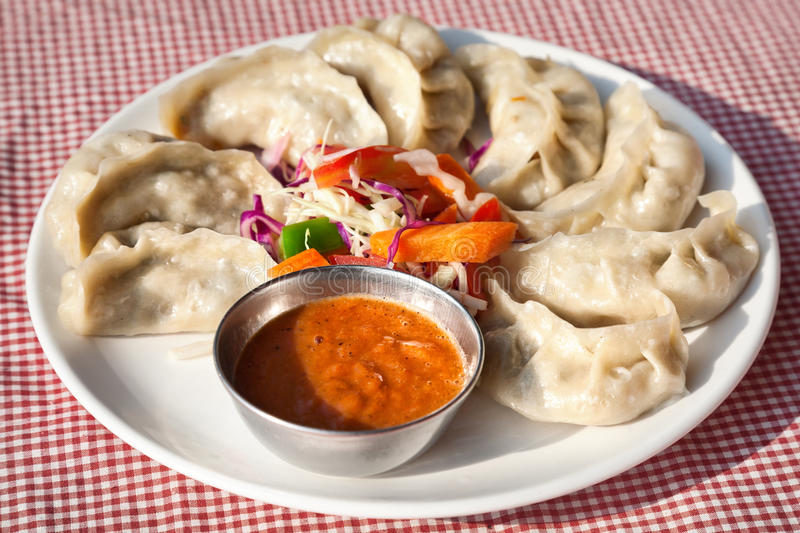 Vegetarian Nepalese momo. Nepalese traditional dumpling momos served with tomato chatni and fresh salad in restaurant royalty free stock image