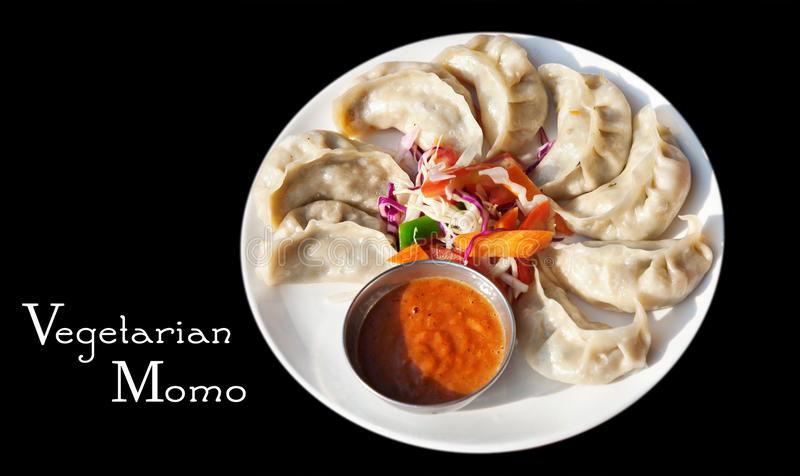 Vegetarian Nepalese momo. Nepalese traditional dumpling momos served with tomato chatni and fresh salad at black background. Free space for your text royalty free stock photo