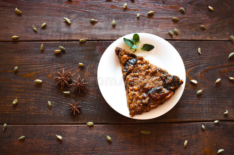 Vegetarian nut pie and spices. The slice of vegetarian nut pie on a white plate lies on a dark wooden background. Around spices cardamom and an anise are royalty free stock photos