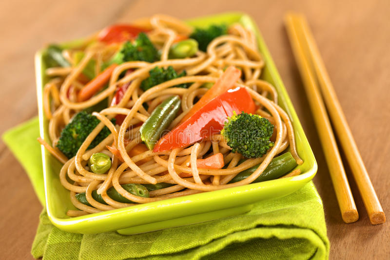 Vegetarian Pasta Stir Fry. Vegetable and wholewheat spaghetti stir fry with chopsticks (Selective Focus, Focus on the broccoli floret in the front royalty free stock image