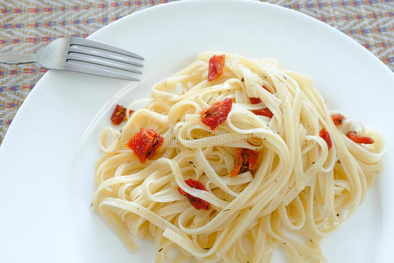 Vegetarian pasta with sun-dried tomatoes. Home cooking. Lunch at home. Pasta and fork on a white plate stock photography
